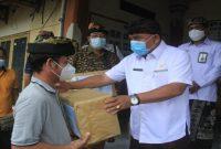Bupati Jembrana I Nengah Tamba menyerahkan bantuan sembako kepada warga terdampak Covid-19